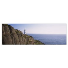 Lighthouse on a rocky coast, Cape Spear, Newfoundl Poster
