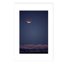 A total lunar eclipse proceeds at dawn over the Mo