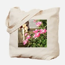 Puppy smelling flowers Tote Bag
