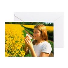Young woman suffering from hay fever in a field -