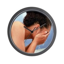 Woman rinsing her face - Wall Clock