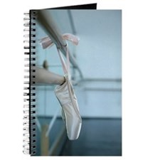 Ballet shoes hanging over a ballet bare Journal