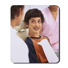 Young boy (8-10) with braces talking to a Mousepad
