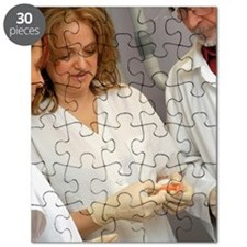 Two female dentists and a male dentist hold Puzzle