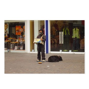 This man was standing in front of a modern clothing store on the main strip in Trier Germany playing his hand organ with his dog at his feet. he had a small cup for donations.