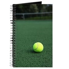 Tennis ball on green court Journal