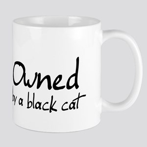 owned by a black cat Mug
