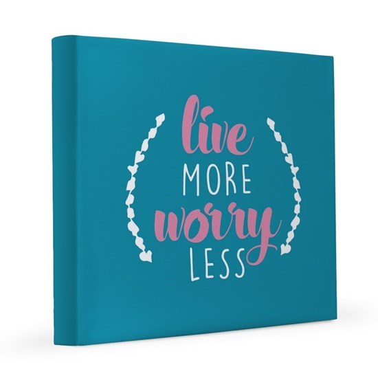 Wall canvas with custom printed blue background and white and pink stylized text that reads: Live More, Worry Less.