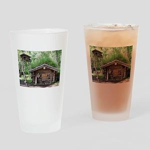 Old log cabin in woods, Alaska, USA Drinking Glass