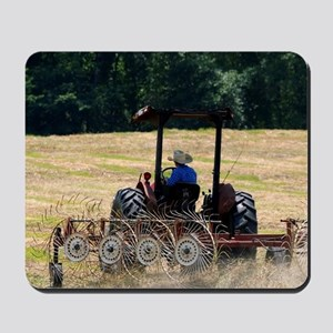 A young boy driving a tractor harvesting Mousepad