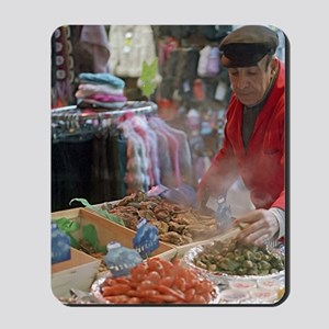 A seafood vendors tends his stall in the Mousepad
