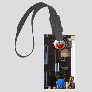 People eat and drink at an outdo Large Luggage Tag