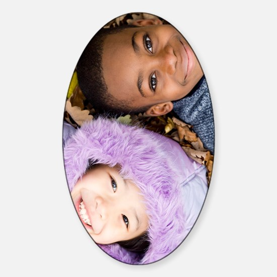 Smiling children lying on autumn le Sticker (Oval)