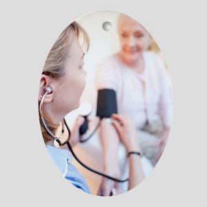 Measuring blood pressure Oval Ornament