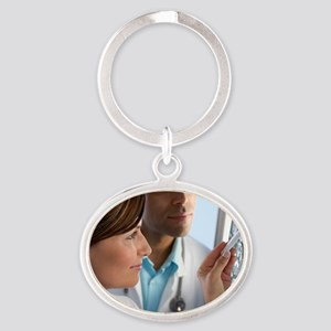Doctors examining MRI scans Oval Keychain