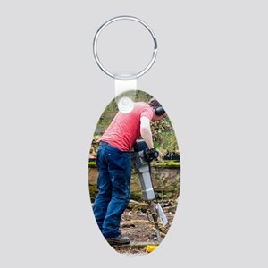 Man breaking concrete with  Aluminum Oval Keychain