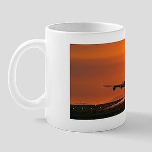 Aeroplane landing at sunset Mug