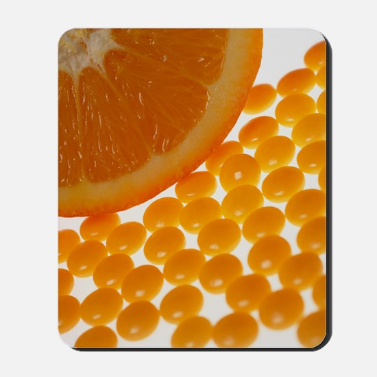 View of vitamin C pills and an orange ha Mousepad