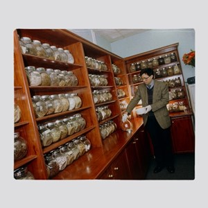 Herbalist in a Chinese herbal medici Throw Blanket