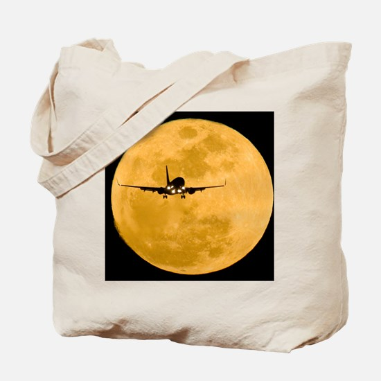 Aeroplane silhouetted against a full moon Tote Bag