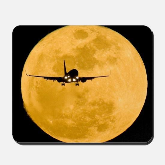 Aeroplane silhouetted against a full moo Mousepad