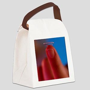 Contact lens seen on a fingertip Canvas Lunch Bag