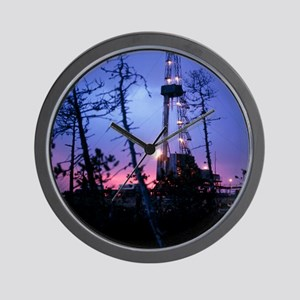Derrick at an oil well in the evening Wall Clock