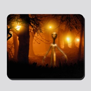 Alien emerging from a forest Mousepad
