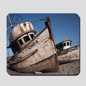 old neglected boats sit beached on sand  Mousepad
