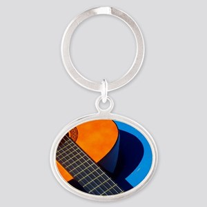 Guitar and its plectrum on a blue ta Oval Keychain