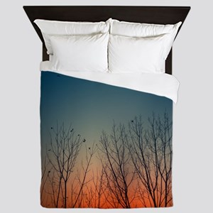 Sunset behind trees with birds flying  Queen Duvet