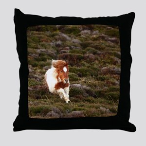Young pony running downhill through h Throw Pillow