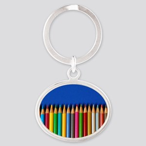 Colorful pencil crayons on blue back Oval Keychain