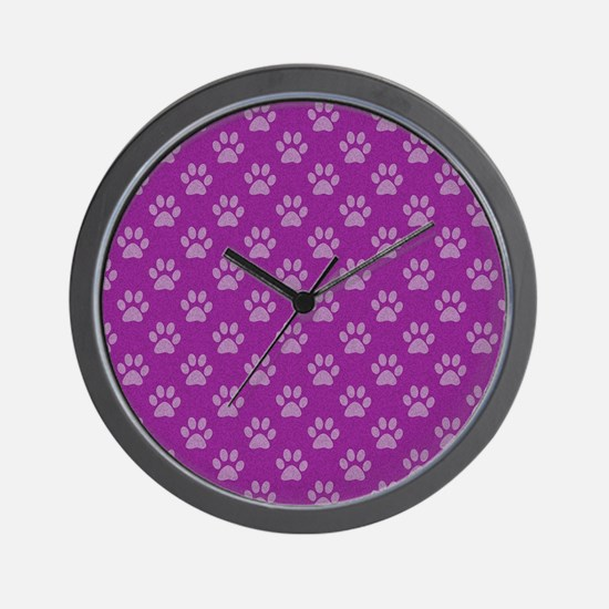 Puppy paw prints on purple background Wall Clock