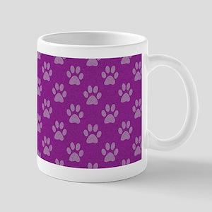 Puppy paw prints on purple background Mugs