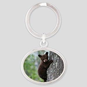 Bear Cub Climbing a Tree Oval Keychain