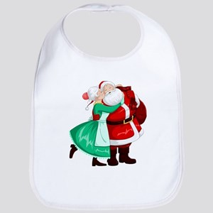 Mrs Claus Kisses Santa On Cheek And Hugs Bib