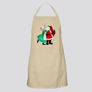 Mrs Claus Kisses Santa On Cheek And Hugs Apron