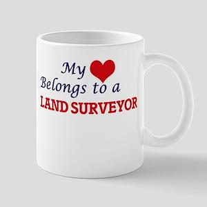My heart belongs to a Land Surveyor Mugs