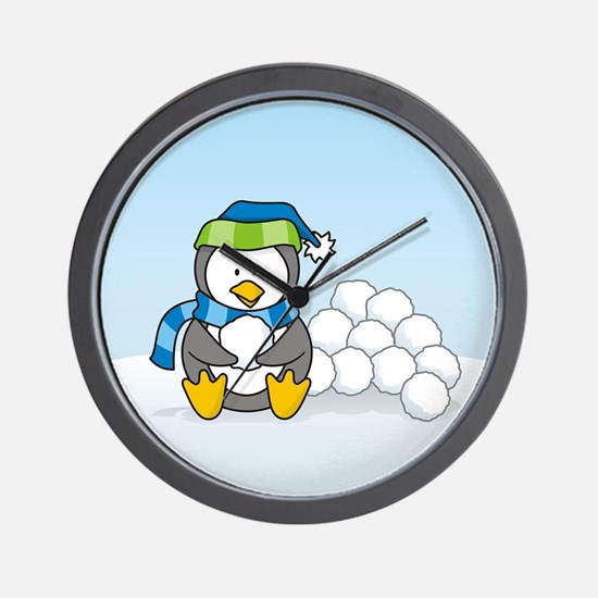 Little penguin sitting with snowballs on snow Wall