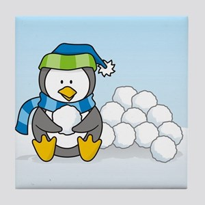Little penguin sitting with snowballs on snow Tile
