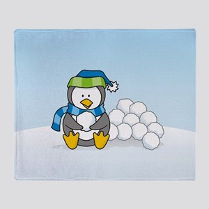 Little penguin sitting with snowballs on snow Thro
