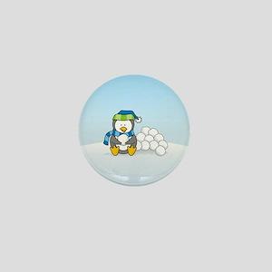 Little penguin sitting with snowballs on snow Mini