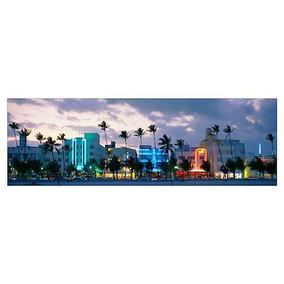 Buildings lit up at dusk, Ocean Drive, Miami Beach Poster