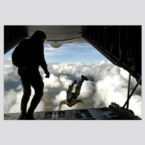Pararescuemen jump out the back of a C130 Hercules