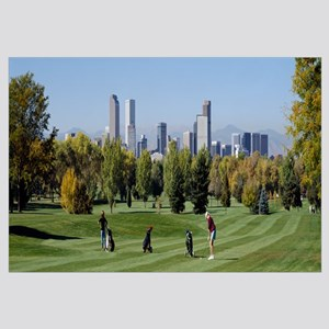 Four people playing golf with buildings in the bac