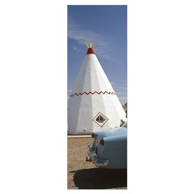 Car with a teepee in the background Wigwam Motel R Poster