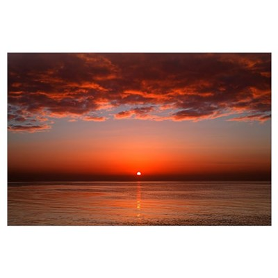 A layer of clouds is lit by the rising sun over Ri Poster