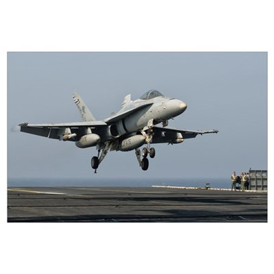 A US Navy F/A-18C Hornet prepares to land aboard U Poster