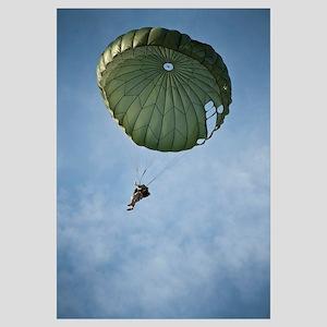 An Airman descends through the sky with parachute